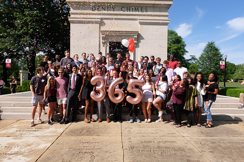 Capstone men and women pose infront of Denny Chimes