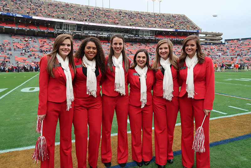 Six women outside posing on the football field.