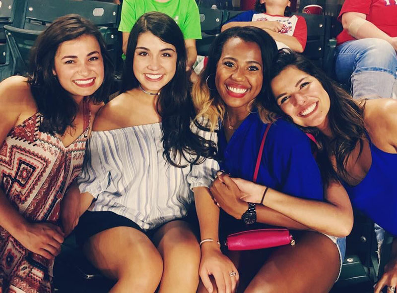 Four girls in casual attire smile at the camera in the stands.