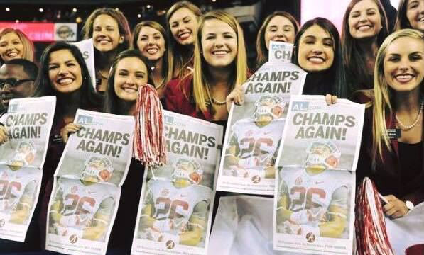 A group of girls hold papers that read 'Champs Again'.