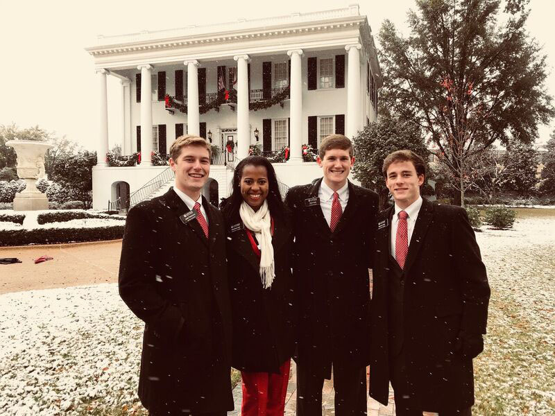 A woman and three men pose in front of the President's Mansion on a snowy day.