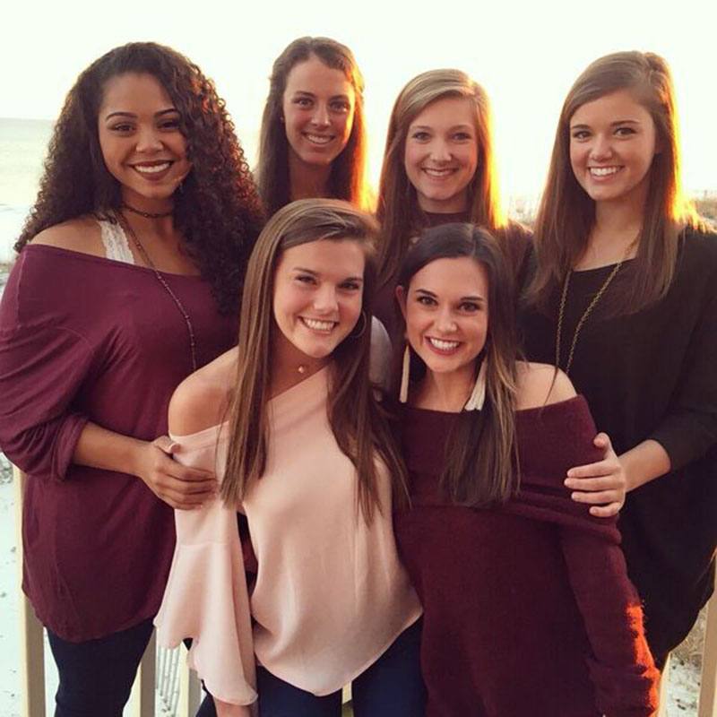 A group of six girls in maroon attire smile for the camera.