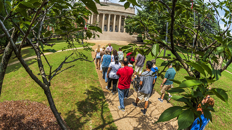 The Capstone men and women guide a tour near Gorgas Library.
