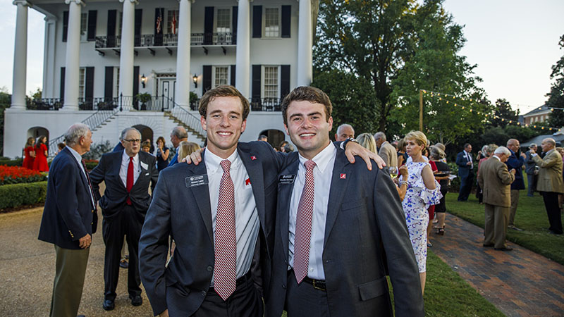 Two men pose in front of the President's Mansion.