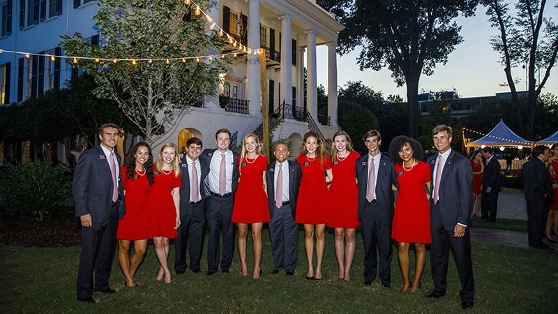 Small group poses in front of the President's Mansion in the evening.