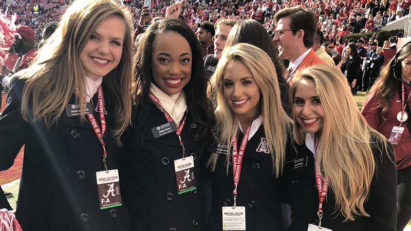 Four women in black coats pose in the stands.
