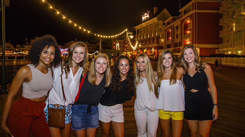 Group of women in casual clothing pose outside at night.