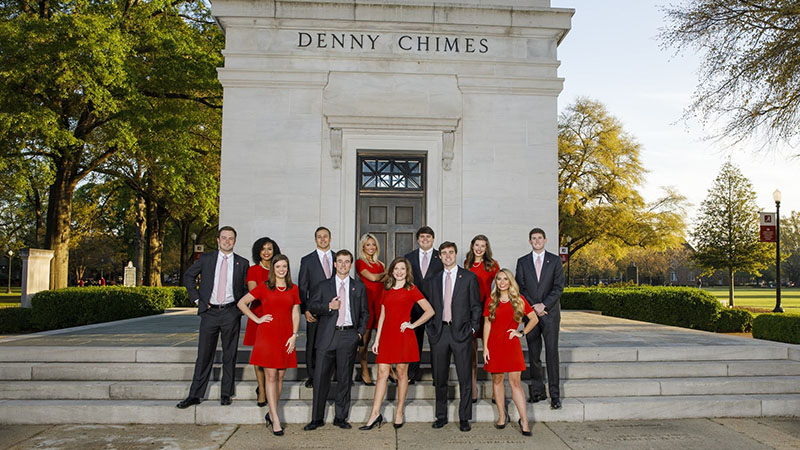 Small group poses in front of Denny Chimes.