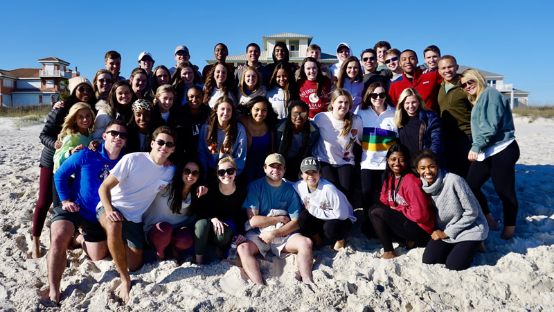 Capstone men and women pose at the beach